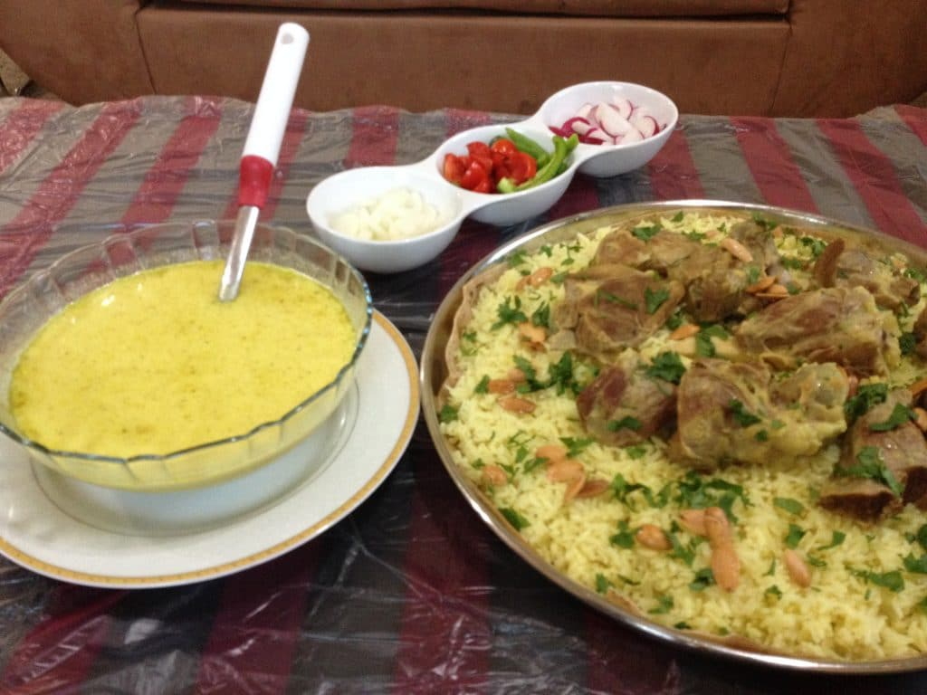 Mansaf, served with Jameed sauce and fresh vegetables